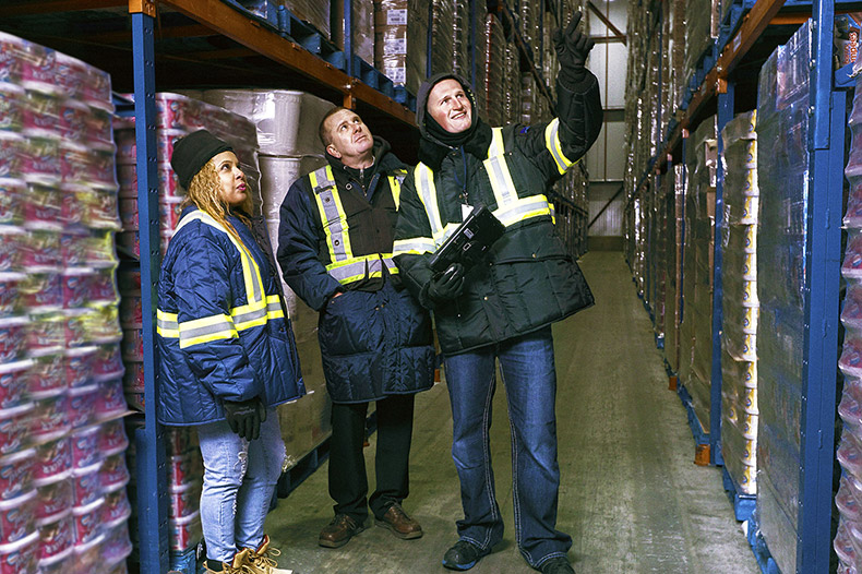 Three warehouse workers gesturing to and talking about products on the shelves.